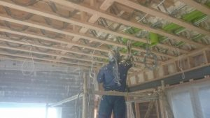 Person spraying insulation in ceiling