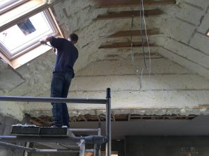 Man spraying insulation in Loft